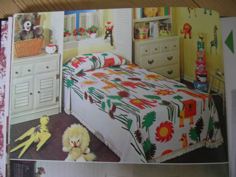 A boldly-patterned and colored bedspread provides the major color scheme for delightful child's room.